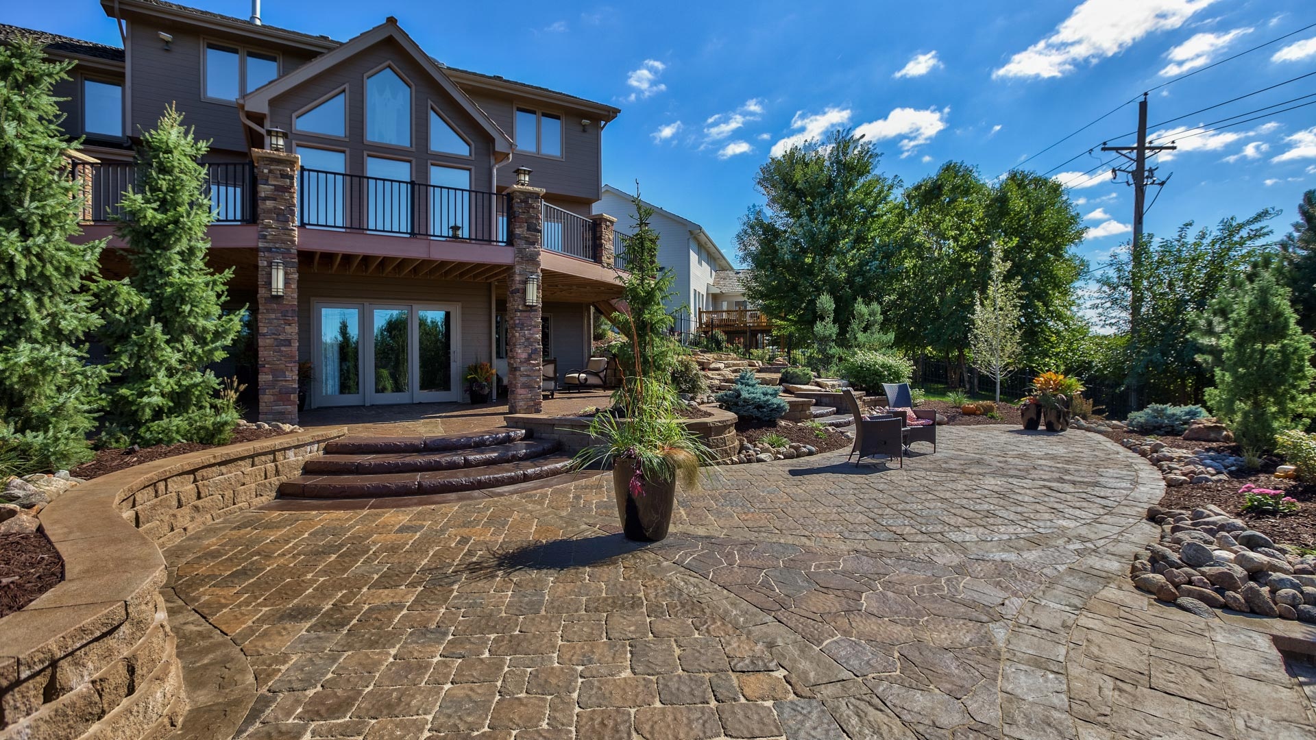 A large paved patio with steps and retaining walls nearby a home in Papillion, NE.