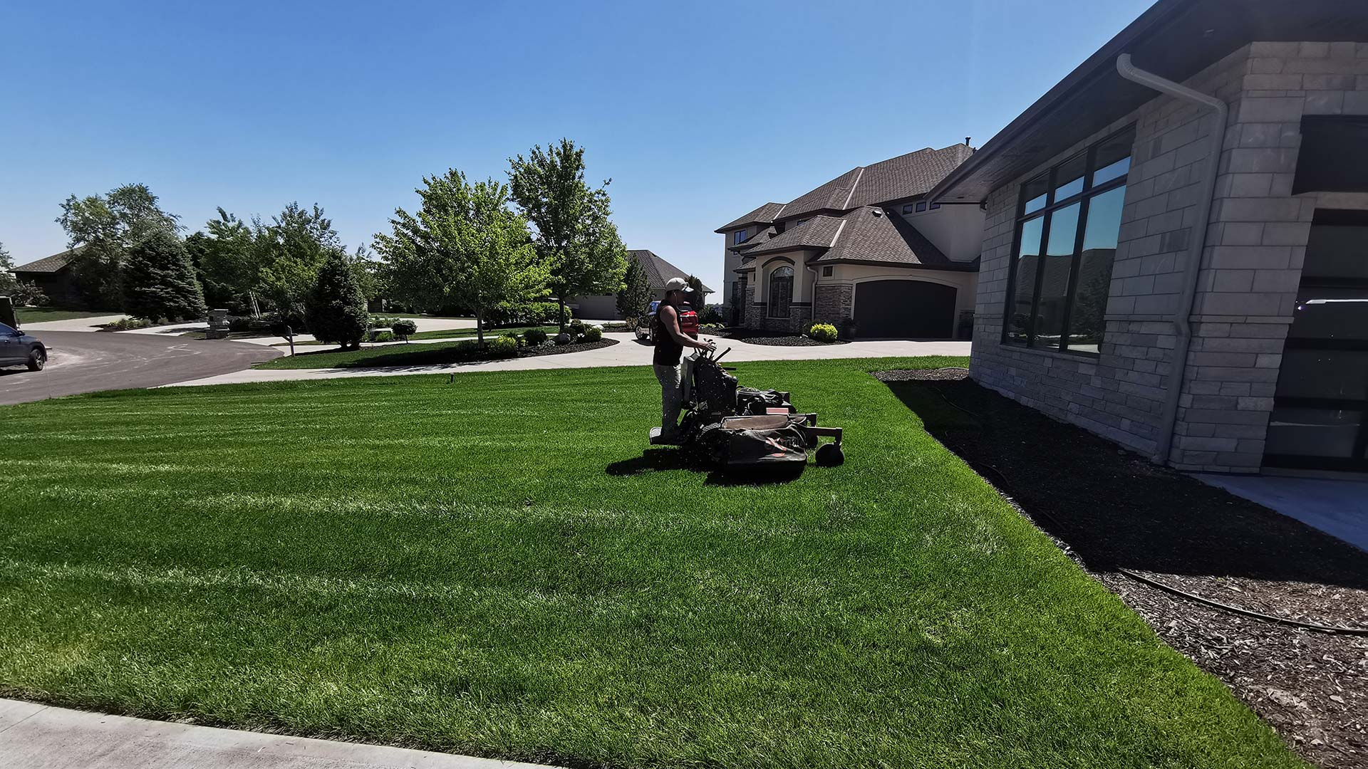 Our landscaper on a lawn mower near a home in Valley, NE.