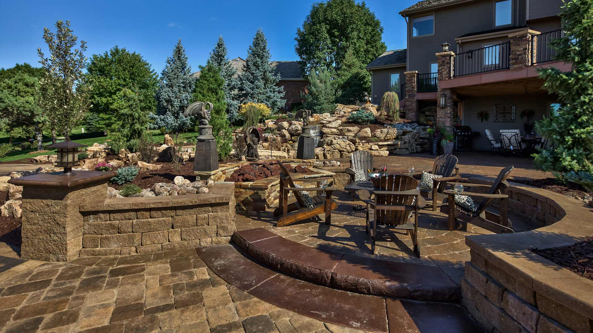 Outdoor living space with seating wall, patio, and stonework in Omaha,  NE.